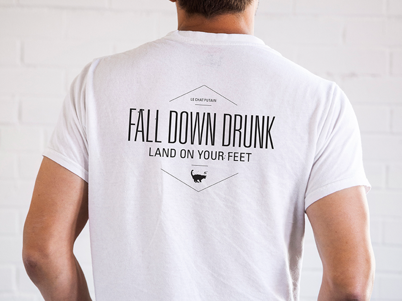 "Le Chat Putain t-shirt back: ""Fall down drunk, land on your feet"""
