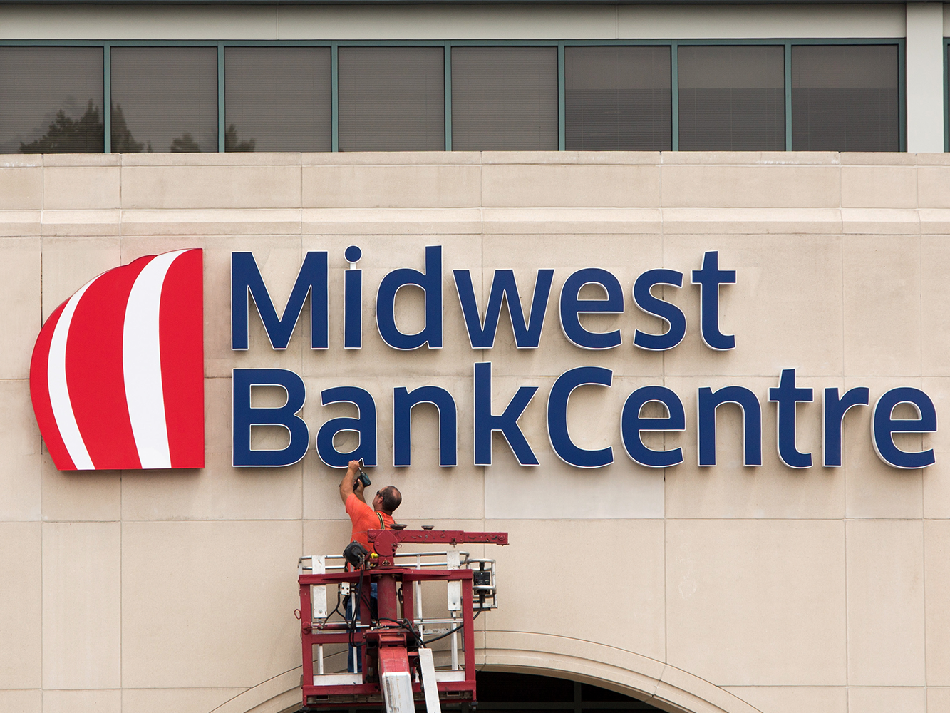 Worker installing Midwest BankCentre storefront signage