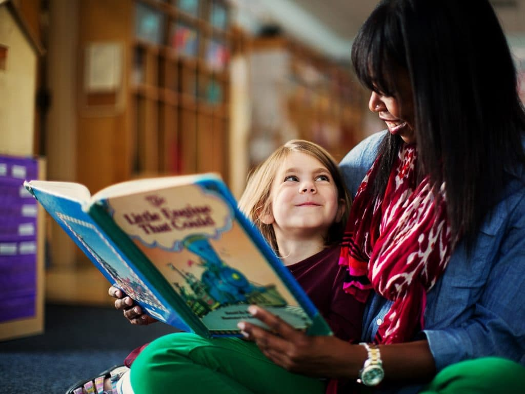 Community School Teacher Reading to Student