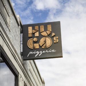 Outdoor signage of logo for Hugo's Pizzeria