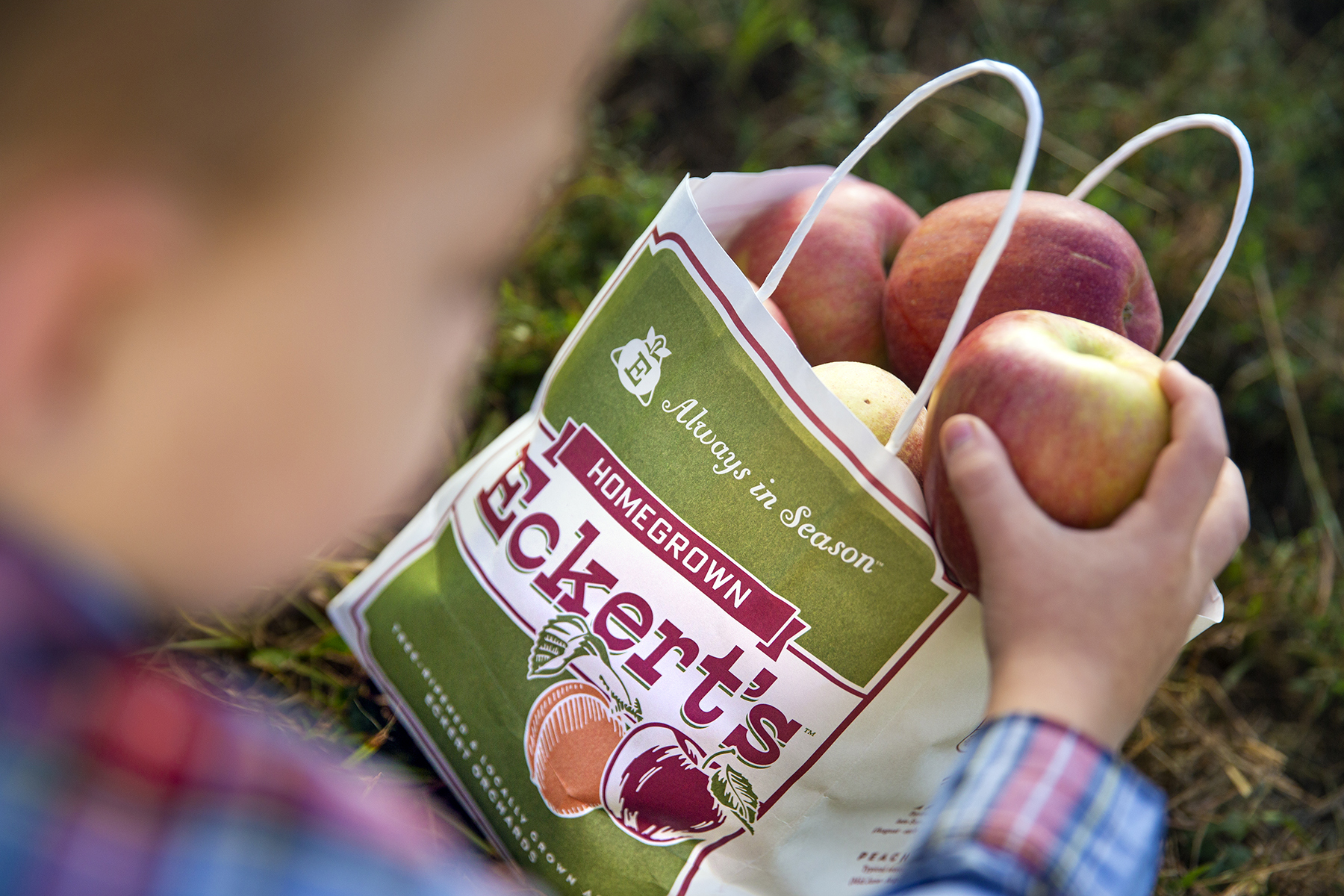 Child placing apple into branded bag